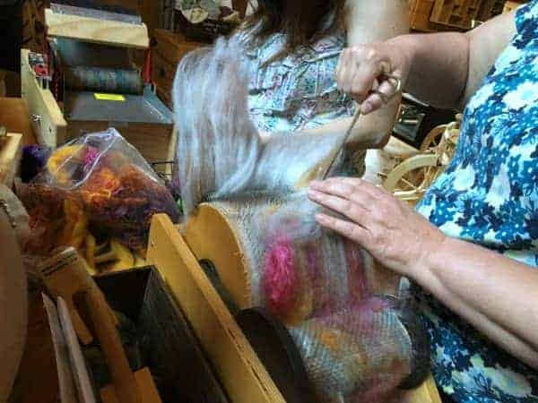 Ginny of Fat Cat Knits removing her batt from the drum carder.