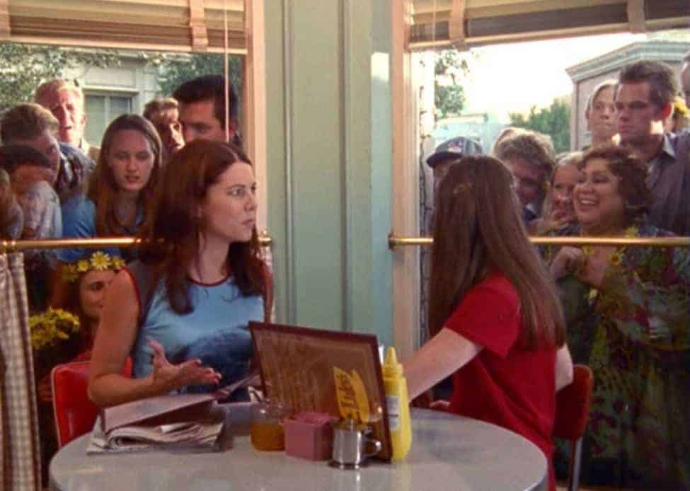 Lorelai Gilmore wearing one of her signature baseball tees in an early-season Luke's Diner scene.