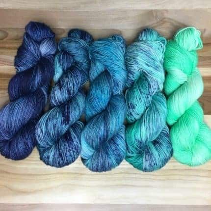 An aqua to dark blue fade of yarn