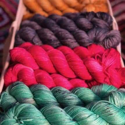 A box of orange, purple, pink and green yarn.