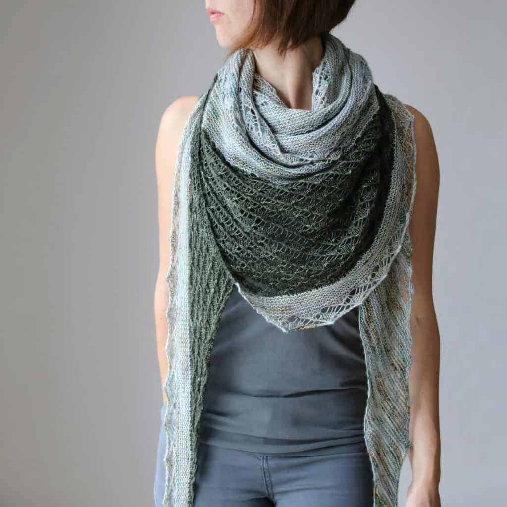 A woman wears a green and gray lace shawl.