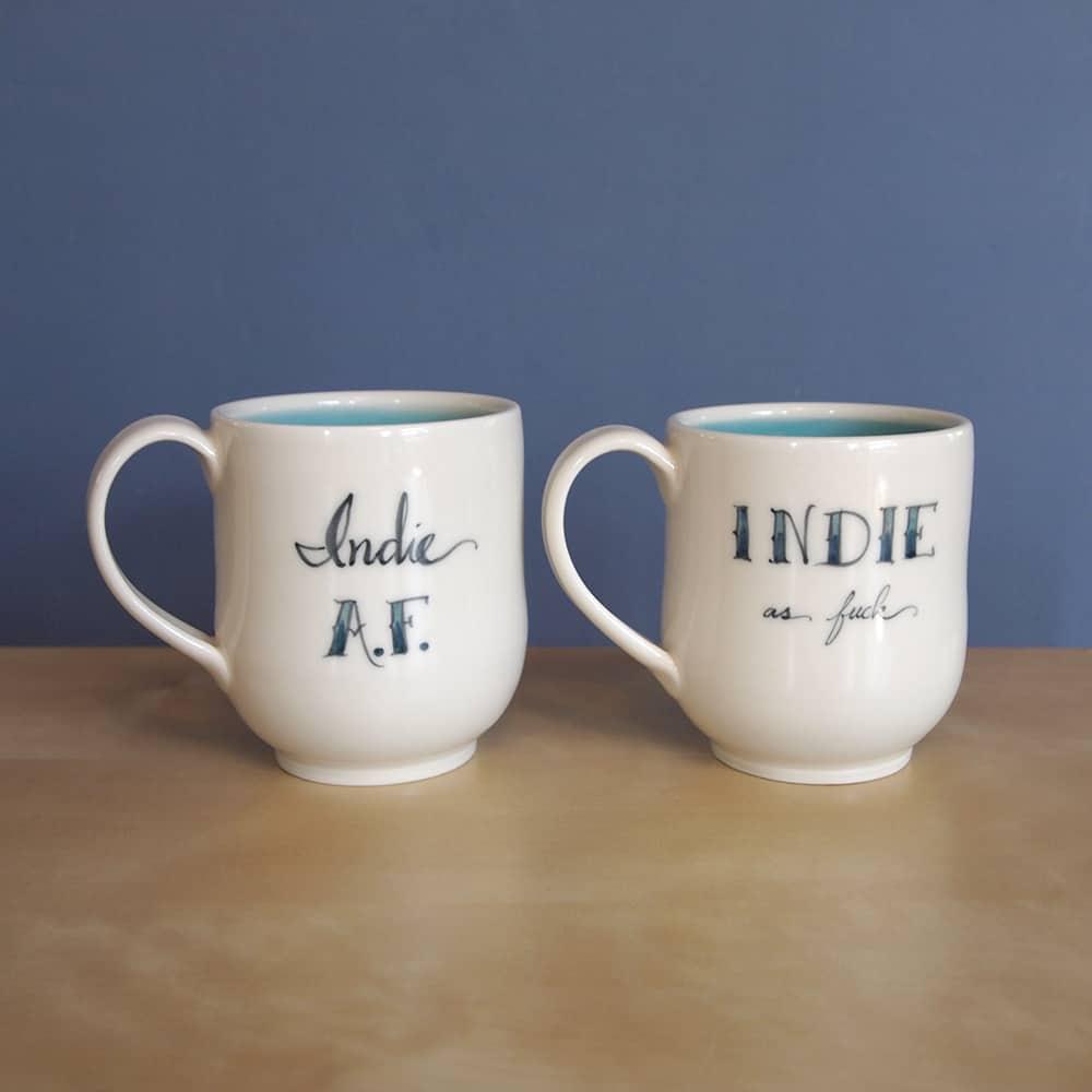 White mugs that say Indie AF and Indie as fuck.