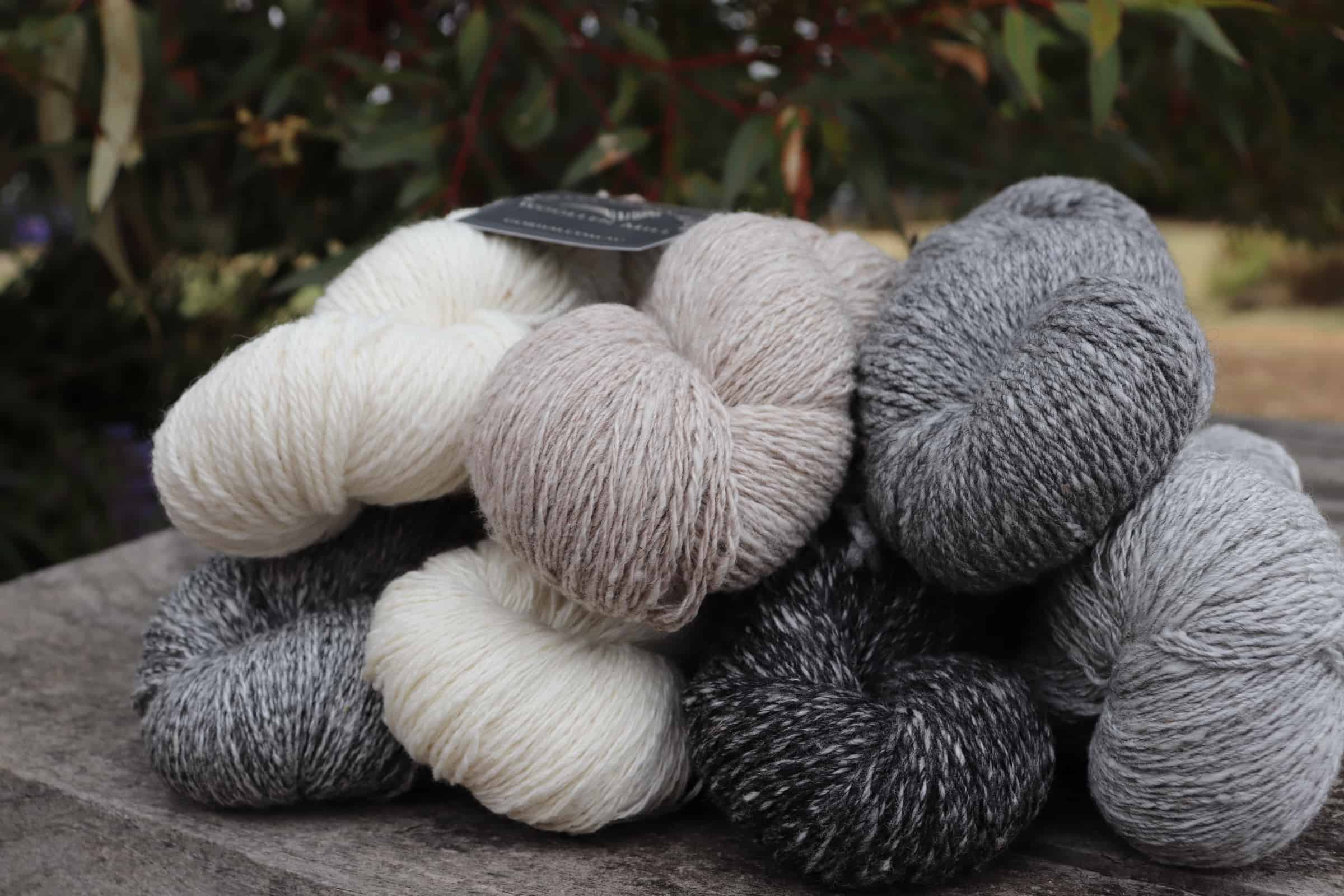 Skeins of white, tan and gray yarn.