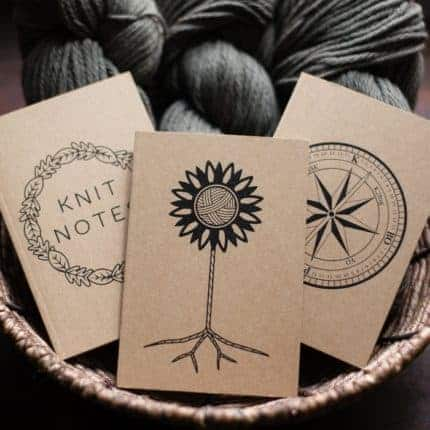 A set of knitting notebooks in front of gray yarn.