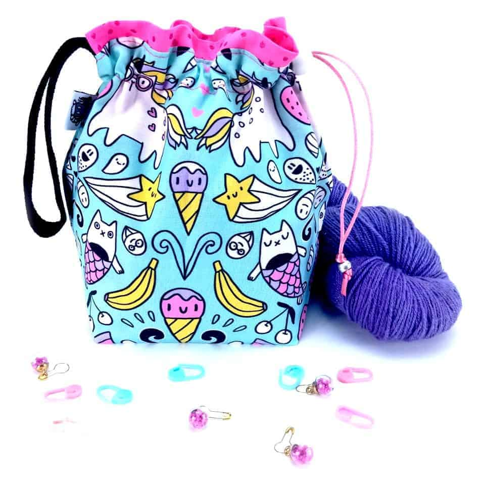 A drawstring bag with an aqua, purple and pink pattern.