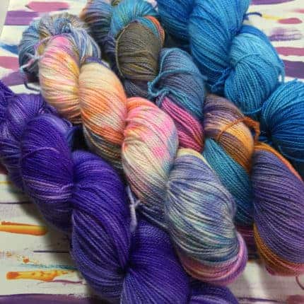 Four skeins of yarn in purple, blue, pink and orange variegated colorways.