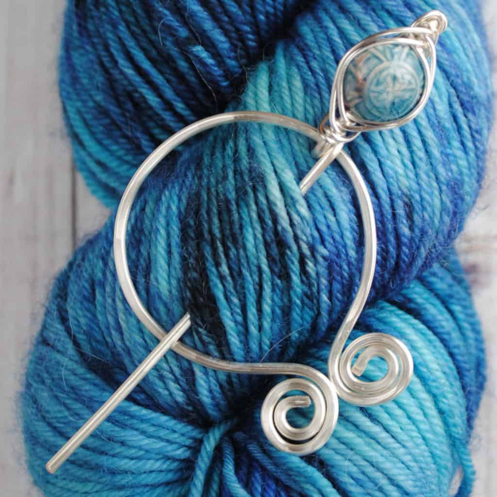 A skein of blue yarn with a silver shawl pin.