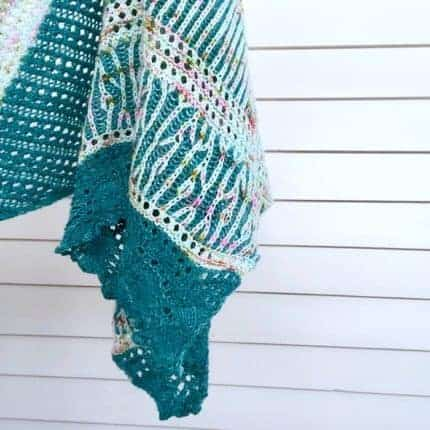 A brioche shawl in teal with pink speckled yarn.