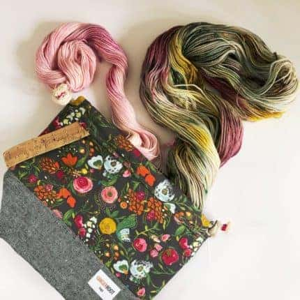 A bag in floral fabric with skeins of pink and green yarn.