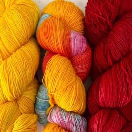 Yellow, yellow and pink variegated and red yarn.