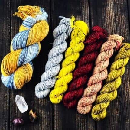 A set of grey, yellow, red, pink and gold mini skeins of yarn.