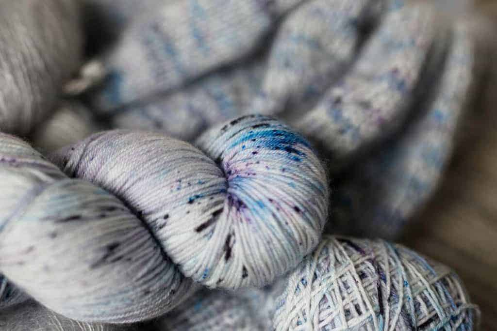 A skein of white yarn with blue, gray and purple speckles.