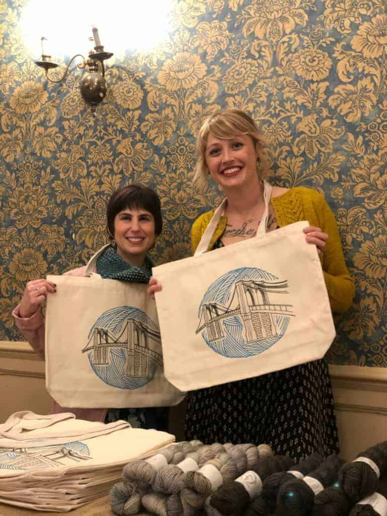 Lisa of Indie Untangled and Andrea Mowry post with tote bags featuring the Brooklyn Bridge over a yarn ball.
