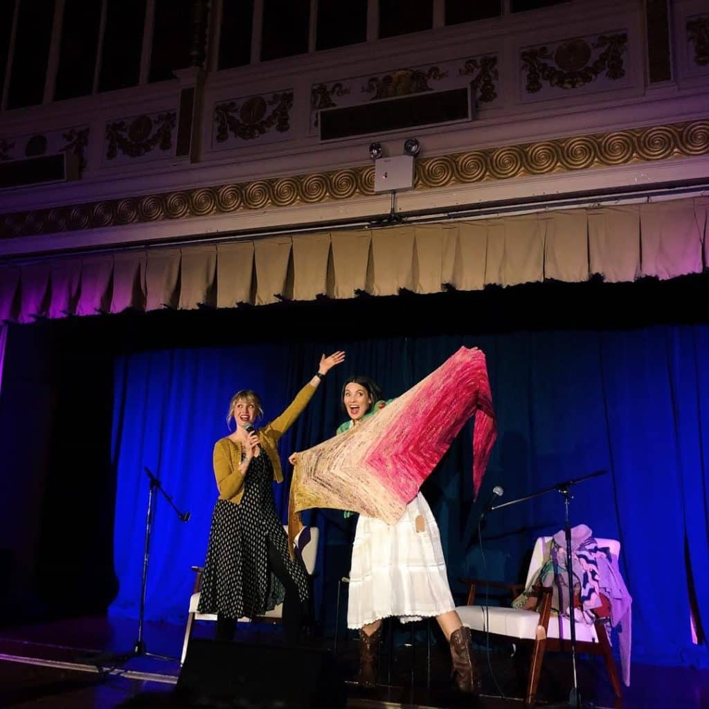Two women pose onstage with a large triangular shawl in pink and mustard yellow.
