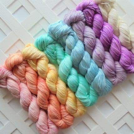 Eight skeins of pastel-colored yarn.