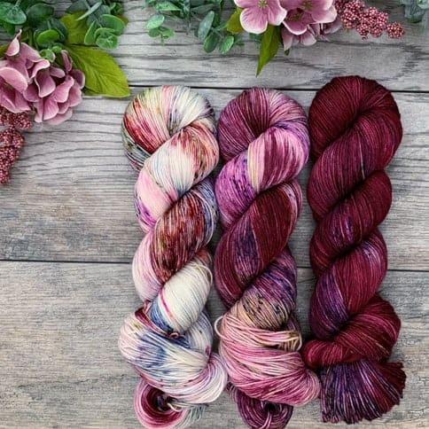 A set of three skeins of burgundy and pink yarn.
