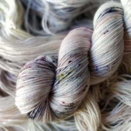 A skein of white yarn with gray and purple speckles.