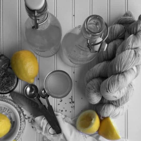 A black and white image of yarn on a table with yellow lemons.
