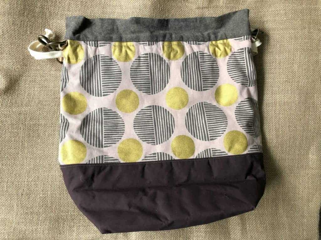 A large drawstring bag with a lilac, gray and gold print.