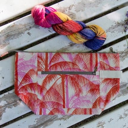A small zipper bag with a red and pink palm tree print.