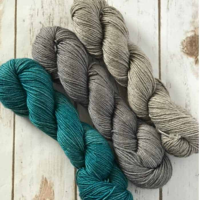 A trio of teal and gray yarn