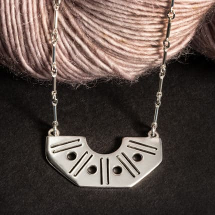A fan-shaped necklace with dots and crochet hooks sits over a skein of light pink yarn.