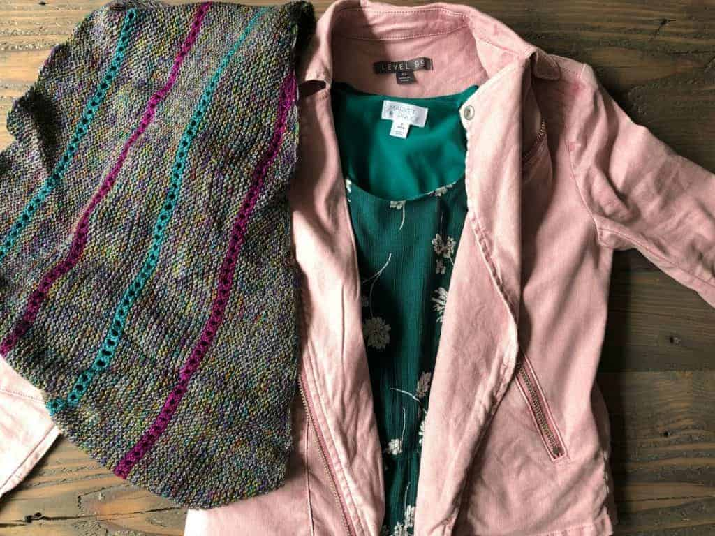 A green floral dress with a pink moto jacket and a grey, purple and teal shawl.
