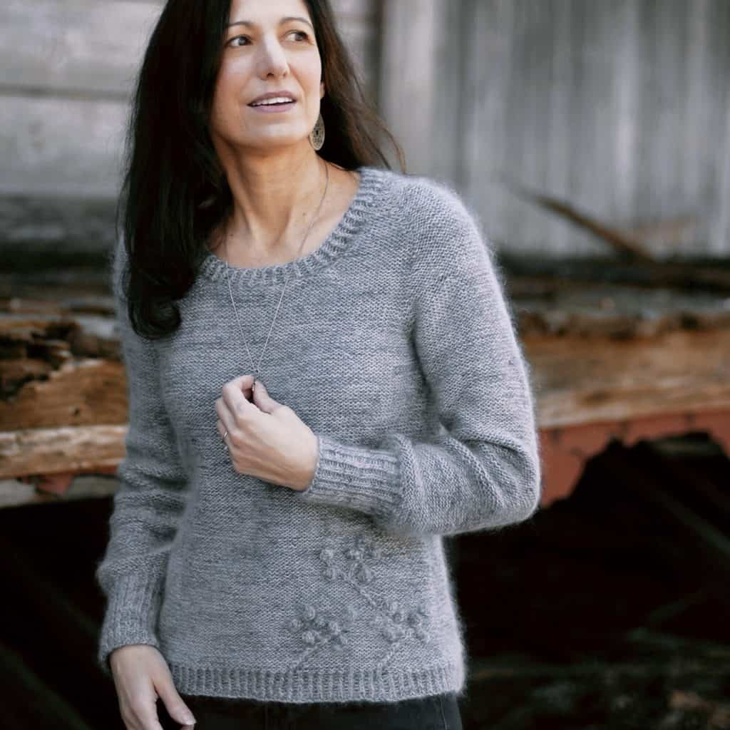 A woman models a fuzzy gray sweater with a branch motif at the hem.