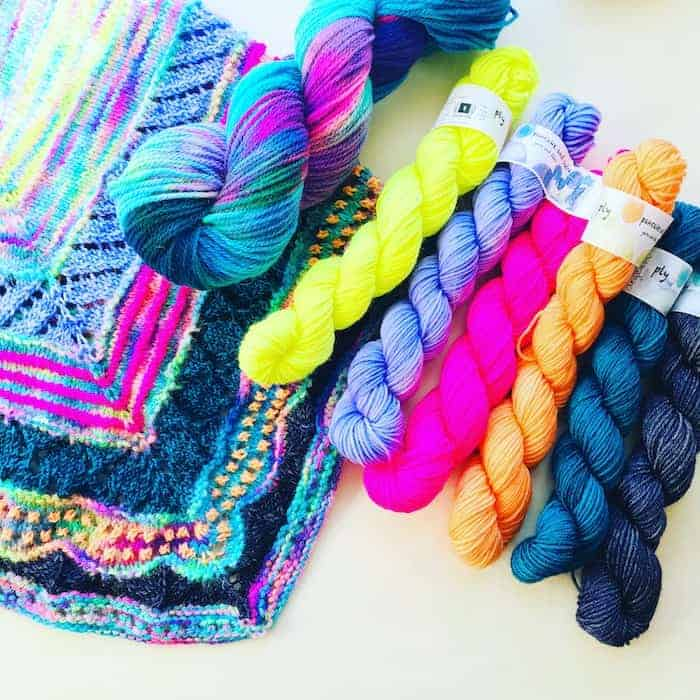 A set of fluorescent yellow, purple, pink, orange and teal yarn with a shawl using the same colors.