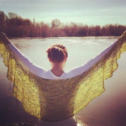 A woman holds a green crescent shaped shawl in front of a body of water.