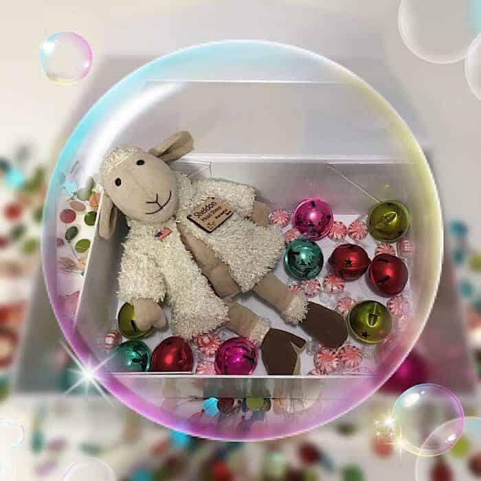 A stuffed sheep surrounded by Christmas ornaments