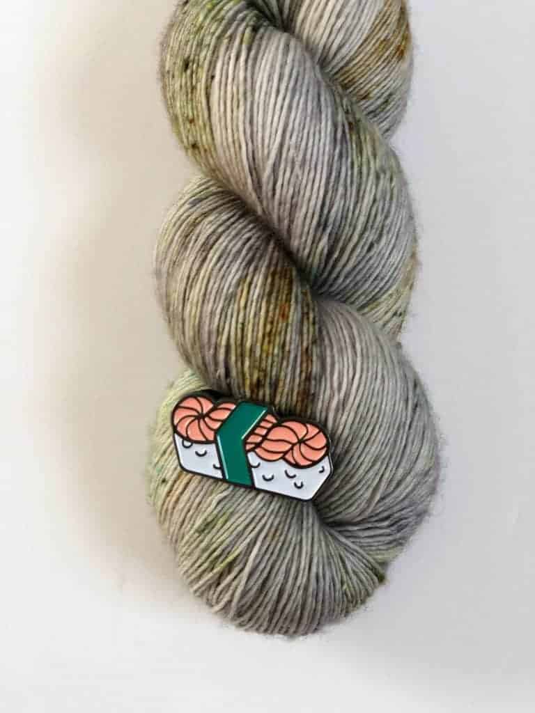 A pink skein of yarn sushi enamel pin.