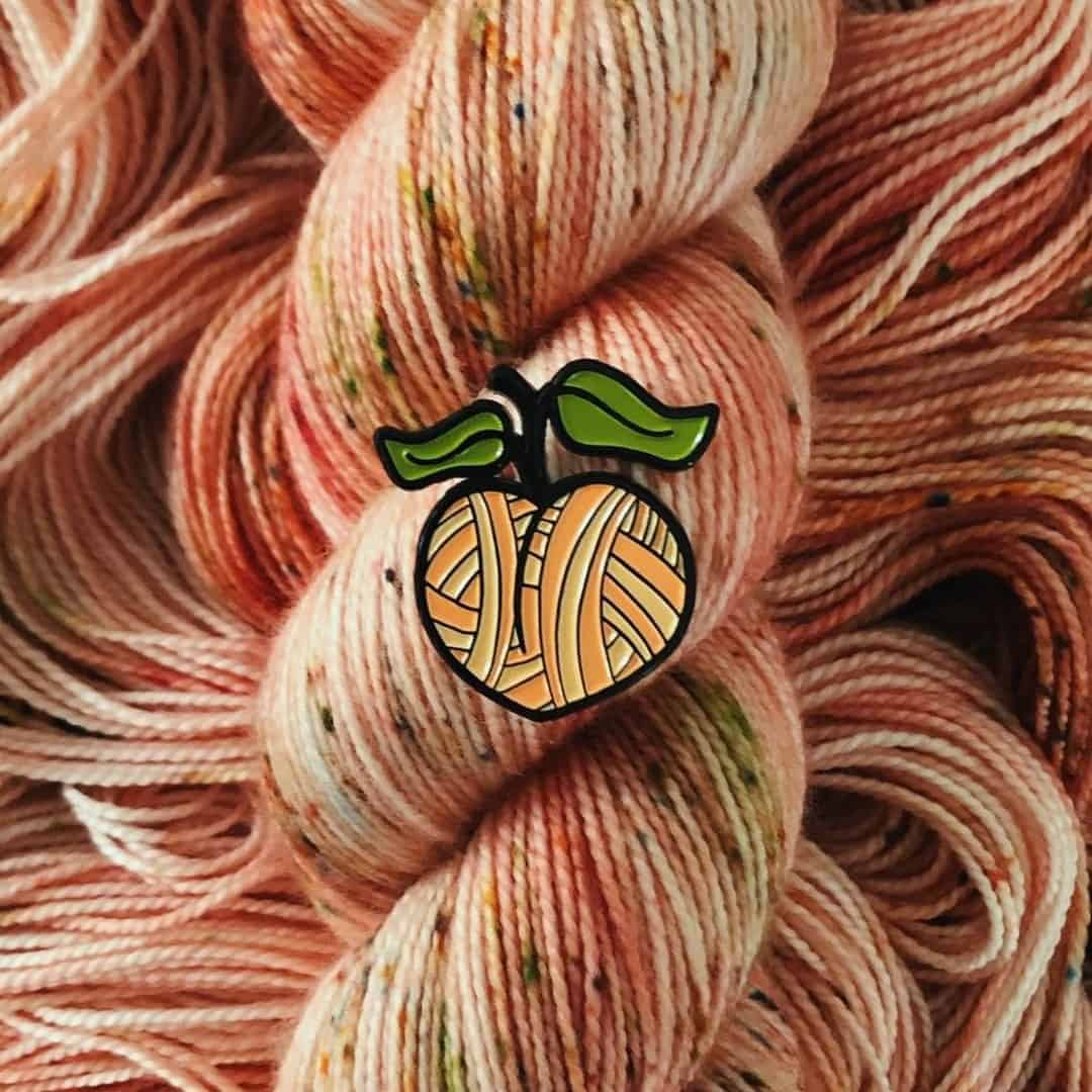 A peach pin over peach colored speckled yarn.