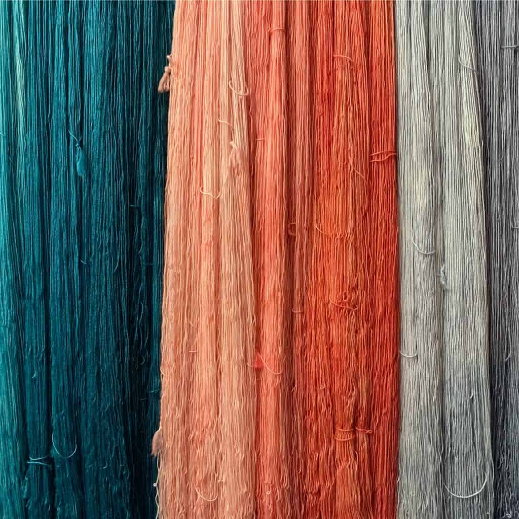 Hanks of teal, orange and grey yarn.