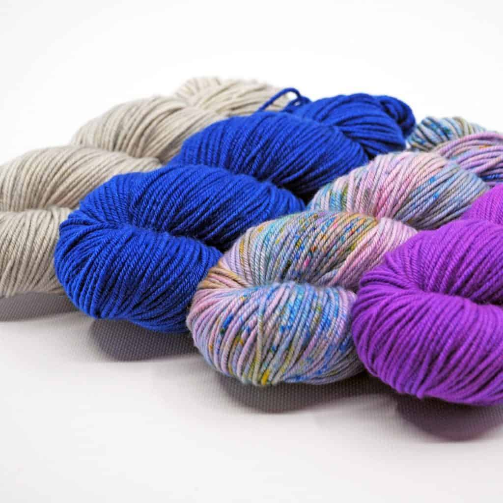 Hanks of grey, bright blue, variegated purple and blue and purple yarn.