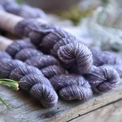 A set of five skeins of purple yarn with sparkles.