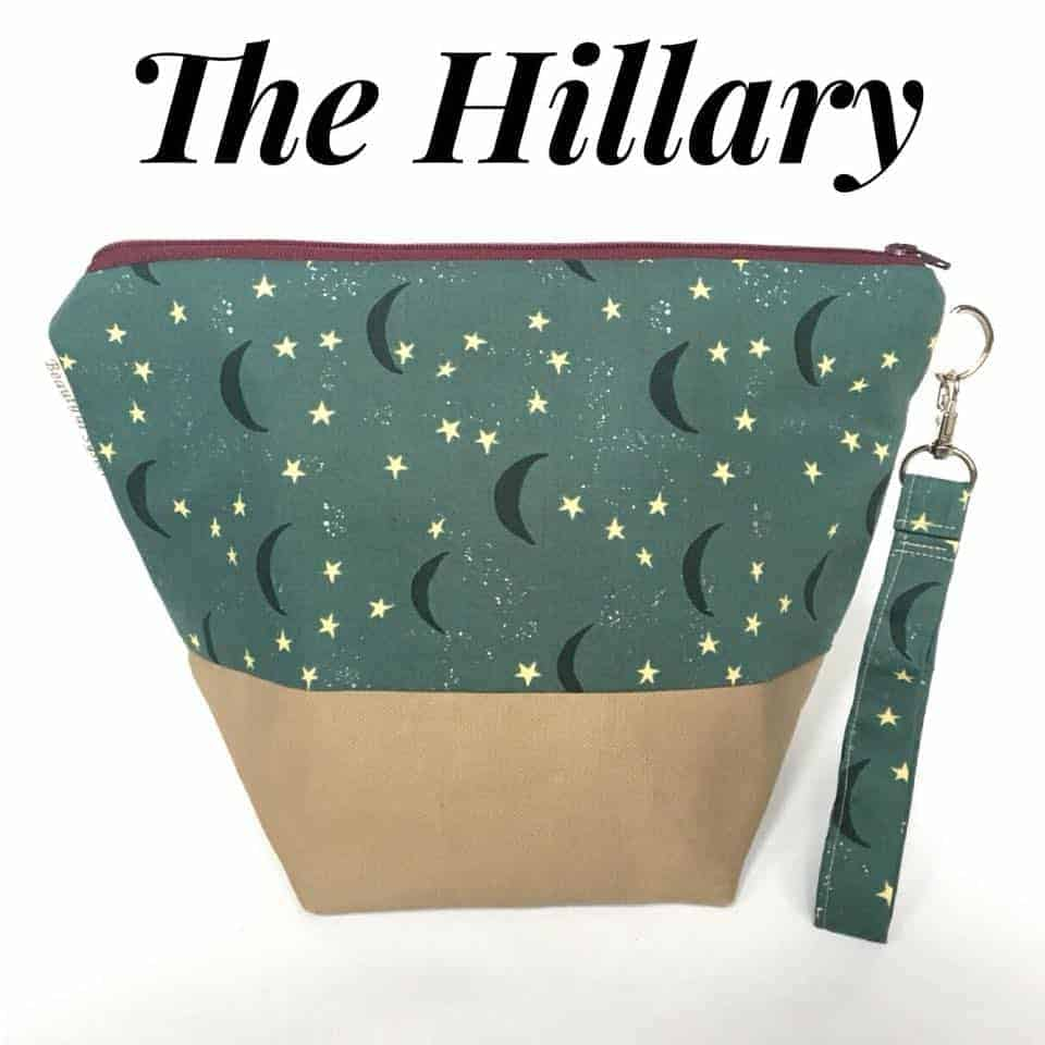 A zipper bag with a green and blue bird fabric with the text The Hillary.