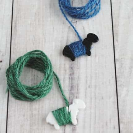 Tiny black and white sheep holding blue and green yarn.