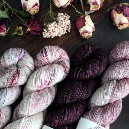 A set of white yarn speckled with pink and purple and a dark purple skein.