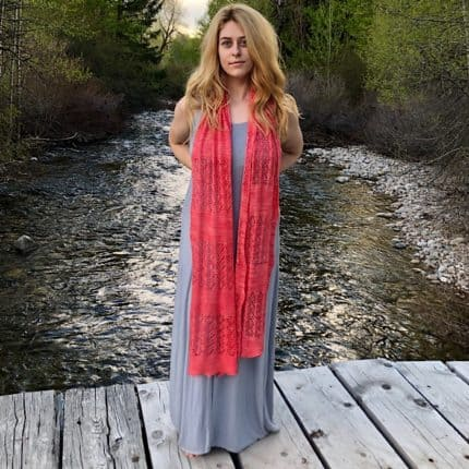 A model in a long gray dress wears a coral lace scarf.