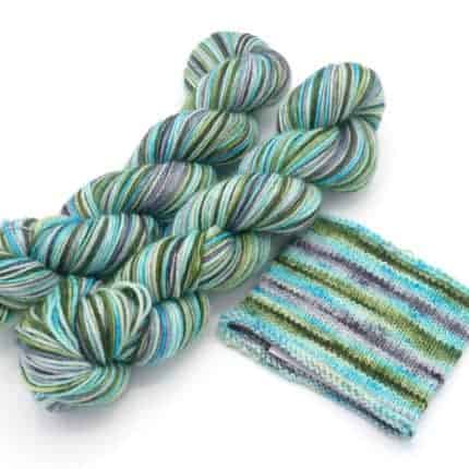 A striping skein of mint green, blue and gray yarn with a swatch.