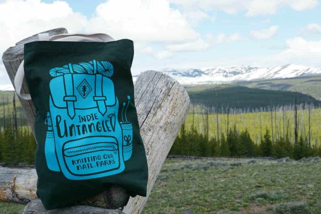 A green tote bag with the image of a turquoise backpack with the words Indie Untangled Knitting Our Natl Parks