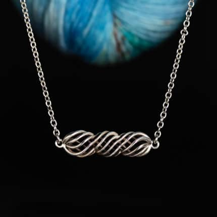 A silver twisted necklace in front of blue yarn.