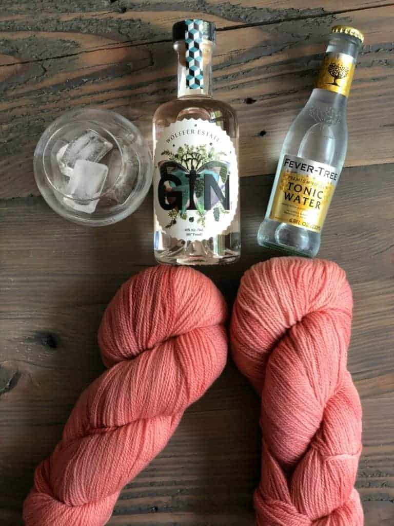 A glass of ice, bottles of Wolffer Estate pink gin and Fever Tree tonic water and two skeins of pink yarn.