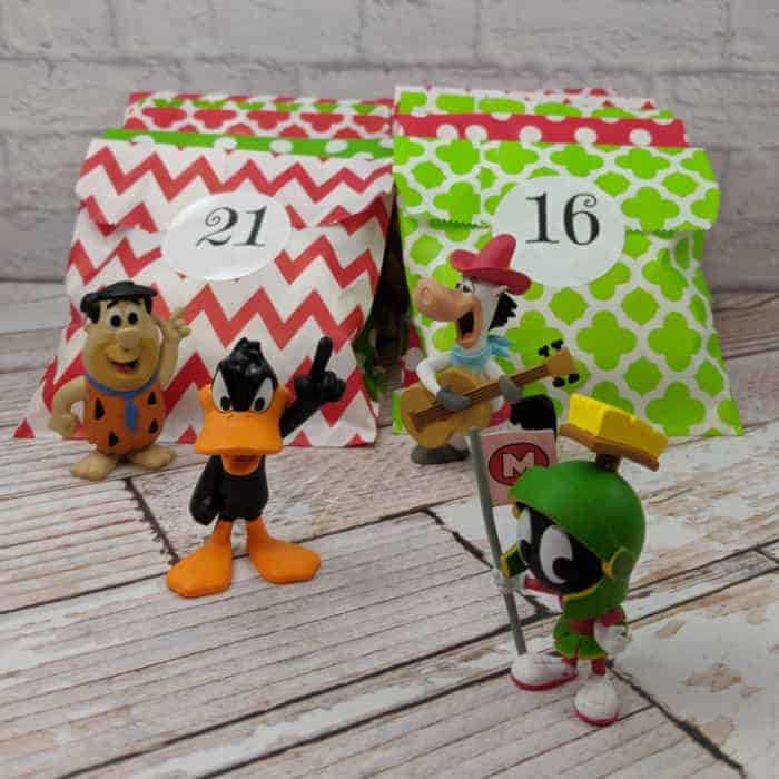 Cartoon character figuers in front of red and green packages numbered 21 and 16.