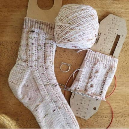 A pink speckled handknit sock on a sock blocker.