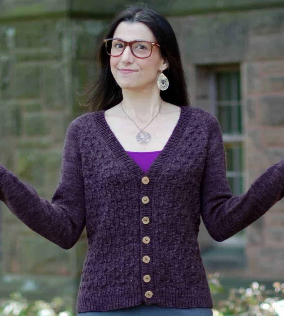 A woman in glasses wears a purple v-neck cardigan.