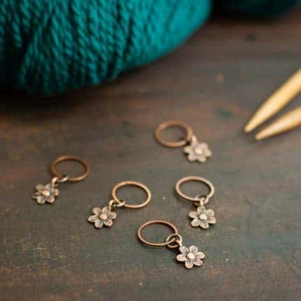 Gold flower stitch markers.