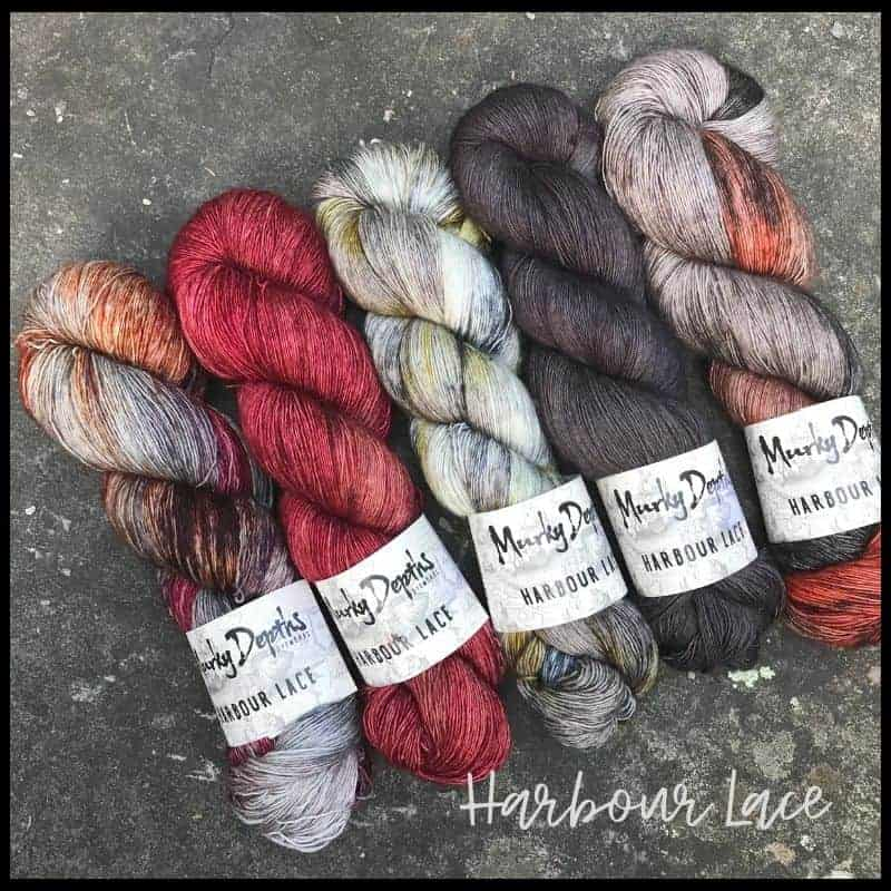 Skeins of variegated, red and gray yarn from Murky Depths