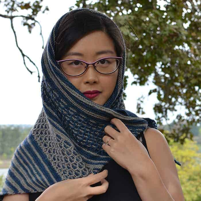 A woman models a blue and gray striped and lace shawl.